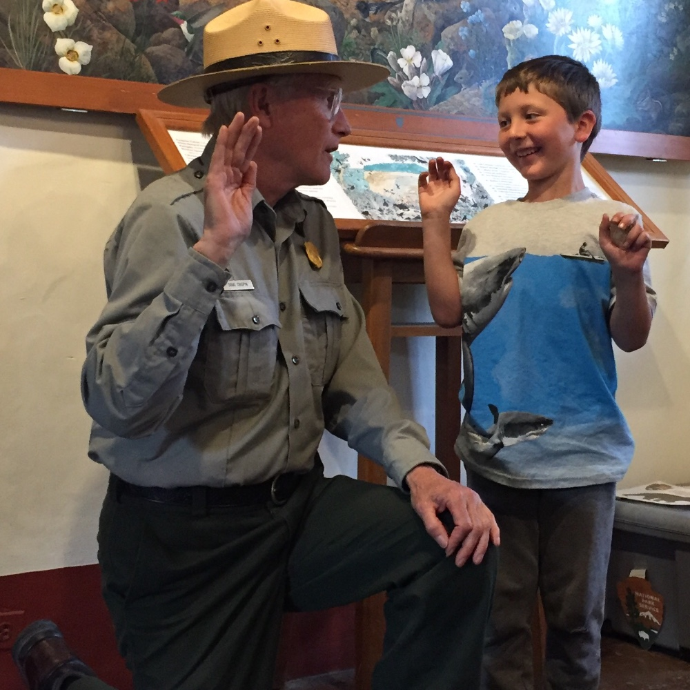 National Parks Ranger saying junior ranger pledge with a boy during a roadschool field trip